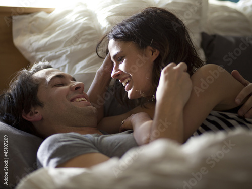 """USA, Utah, Provo, Young couple relaxing in bed"""