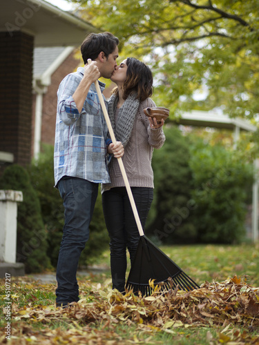 """USA, Utah, Provo, Young couple kissing, raking leaves in garden"""
