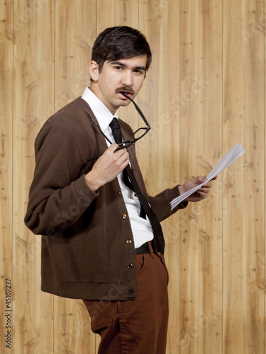 Portrait of businessman reading document in office
