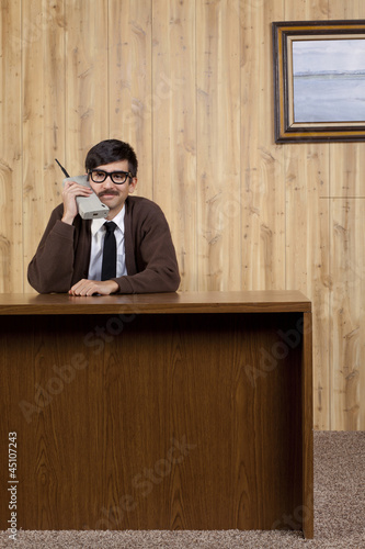Businessman using old fashioned mobile phone in office
