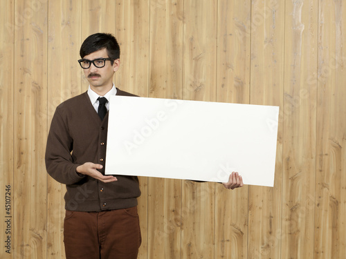 Businessman holding blank placard in office