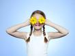 Studio portrait of girl (10-11) shielding eyes by two yellow flowers