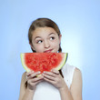 Studio shot of girl (10-11) holding slice of watermelon