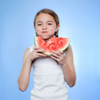 Studio shot of girl (10-11) eating watermelon