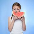 Studio shot of girl (10-11) holding slice of watermelon