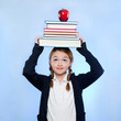 Studio shot of girl (10-11) holding stack of books and apple on head