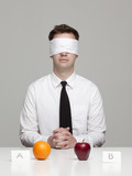 Studio portrait of young man with blindfold choosing between orange and apple