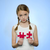 Studio portrait of girl (10-11) holding red jigsaw puzzles