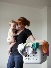"""USA, Utah, Orem, Mother holding baby (6-11 months) and laundry basket"""