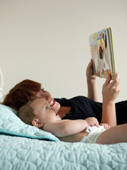 """""""USA, Utah, Orem, Mother reading book with baby (6-11 months)"""""""