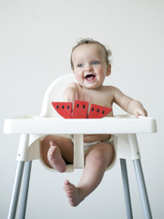 Baby boy (6-11 months) sitting on high chair