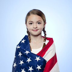 Studio portrait of girl (10-11) wrapped in american flag