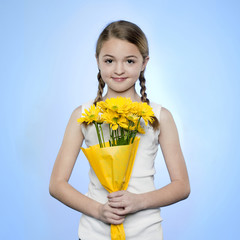 Studio portrait of girl (10-11) holding bunch of yellow flowers