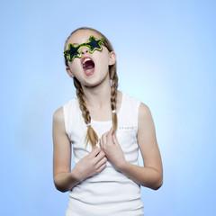 Studio portrait of girl (10-11) wearing star shaped glasses singing