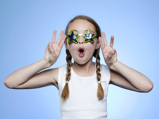Studio portrait of girl (10-11) wearing star shaped glasses cheering