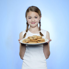 Studio portrait of girl (10-11) holding cookies on plate