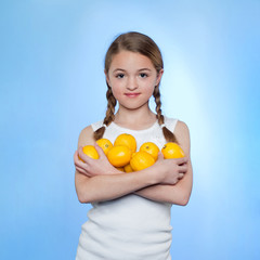 Studio shot of girl (10-11) holding lemons