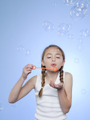 Studio shot of girl (10-11) blowing bubbles