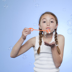 Studio portrait of girl (10-11) blowing bubbles
