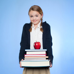 Studio portrait of girl (10-11) holding stack of books and apple