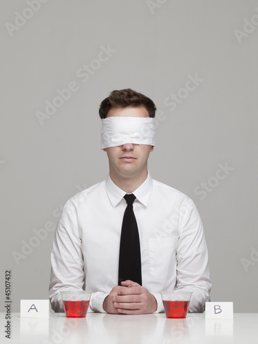 Studio portrait of young man with blindfold sitting in front of two glasses with red liquid