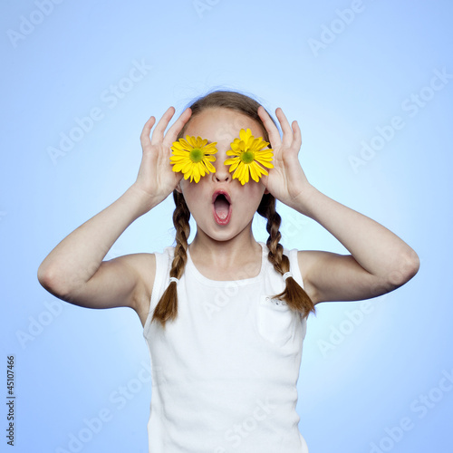 Studio portrait of girl (10-11) shielding eyes by two yellow flowers