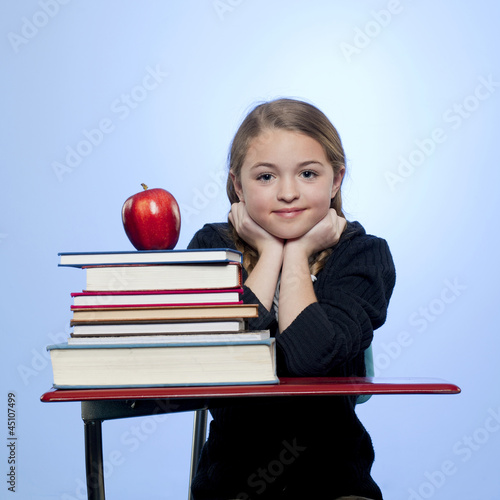 Studio portrait of girl (10-11) with stack of books and apple