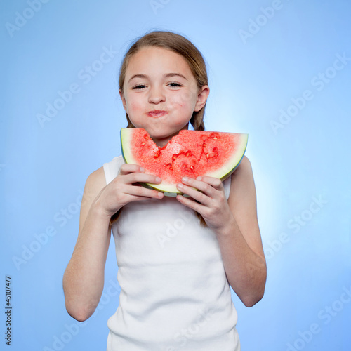 Studio shot of girl (10-11) eating watermelon
