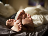 """USA, Utah, Provo, Close-up of feet of couple lying in bed"""