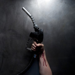 Studio shot of man's hand with blood holding gasoline nozzle