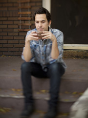 """USA, Utah, Provo, Young man with mug sitting on steps in front of house"""