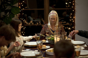 """""""USA, Utah, Cedar Hills, Three generation family with girl (8-9) holding hands at Christmas table"""""""