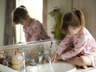 """USA, Utah, Cedar Hills, Girl (4-5) sitting by bathroom sink, rinsing toothbrush"""