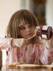 """USA, Utah, Cedar Hills, Girl (4-5) putting jam on bread"""