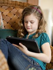 """USA, Utah, Cedar Hills, Girl (8-9) sitting in wicker chair, using digital tablet"""