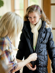 """USA, Utah, Cedar Hills, Mother zipping daughter's (8-9) winter jacket"""