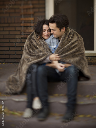 """USA, Utah, Provo, Young couple wrapped in blanket sitting on steps in front of house"""