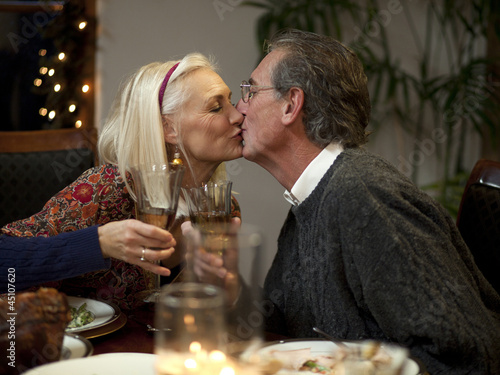 """USA, Utah, Cedar Hills, Senior couple toasting and kissing at table"""