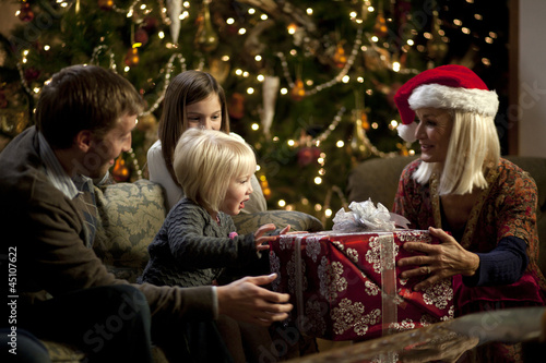 """USA, Utah, Cedar Hills, Three generation family with girls (2-3, 8-9) opening Christmas presents"""