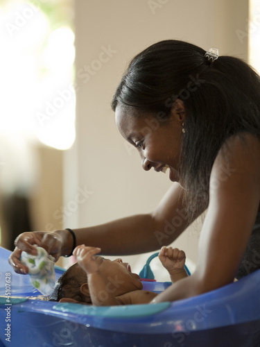 """USA, Utah, Cedar Hills, Mother bathing newborn baby boy ( 0-1 months)"""