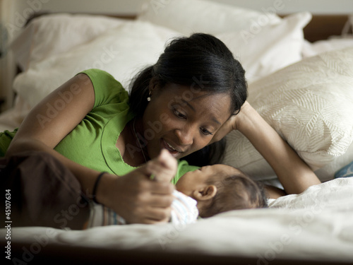 """USA, Utah, Cedar Hills, Mother laying on bed with newborn baby boy ( 0-1 months)"""
