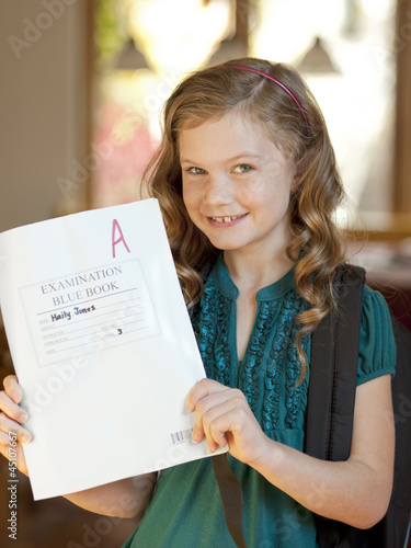 """USA, Utah, Cedar Hills, Girl (8-9) holding book of examination results with A grade"""
