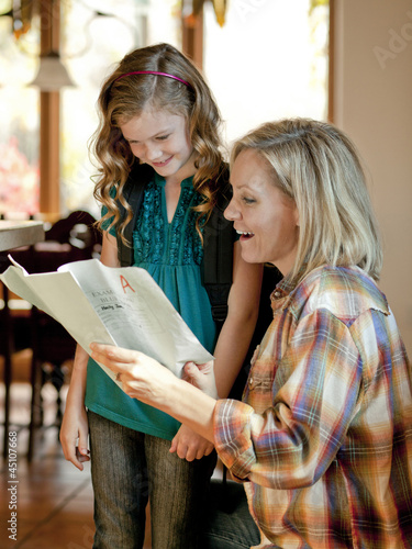 """USA, Utah, Cedar Hills, Girl (8-9) showing examination results with grade A to mother"""