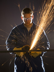 man in blue coveralls with a power grinder