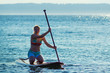 Woman kneeling on Stand Up Paddle Board