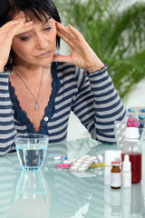 Woman with headache taking her medication