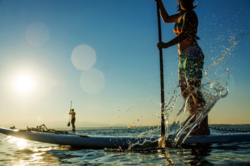 Women on Stand Up Paddle Board with Water Splash
