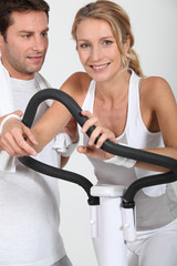 Couple using gym equipment