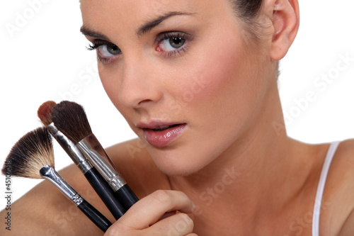 woman holding three make up brushes