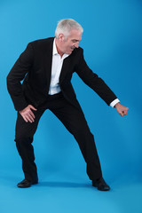 man in suit gesturing on blue background